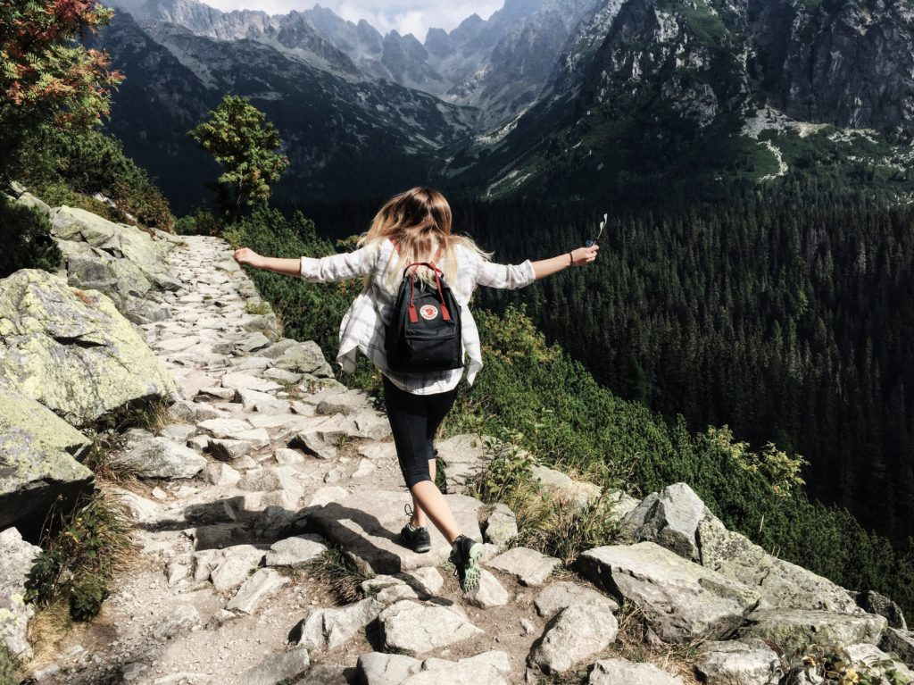 A woman enjoying her hike in beautiful and difficult terrain.